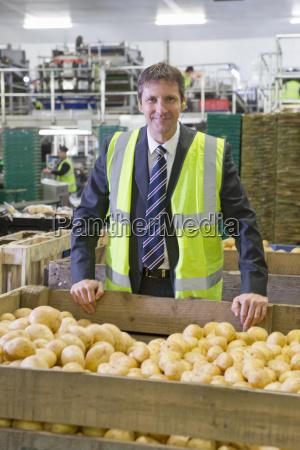 portrait confident supervisor leaning on bin