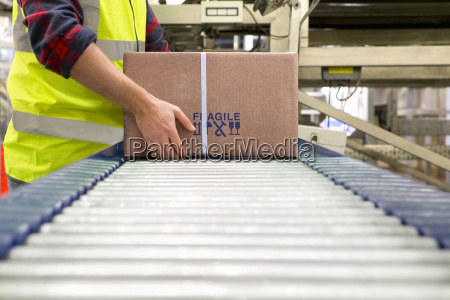 worker processing cardboard box on conveyor