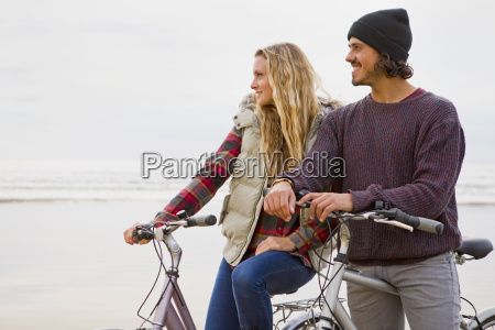 smiling couple with bicycles looking at