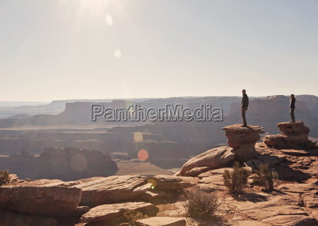 two figures stand at the canyons