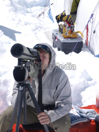 a mountain ranger is looking through