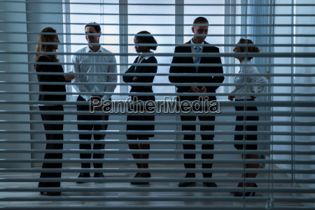 businesspeople talking with each other behind