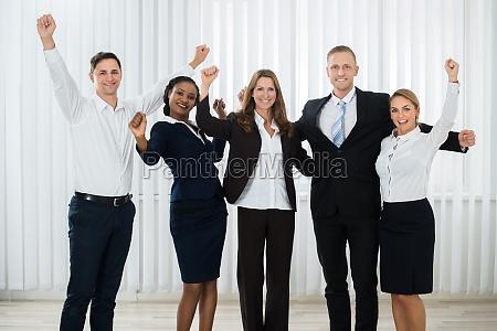 successful businesspeople raising hands