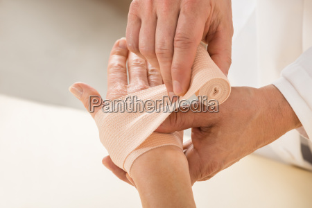 doctor wrapping elastic bandage to patient