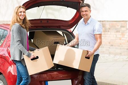 couple putting cardboard box in car