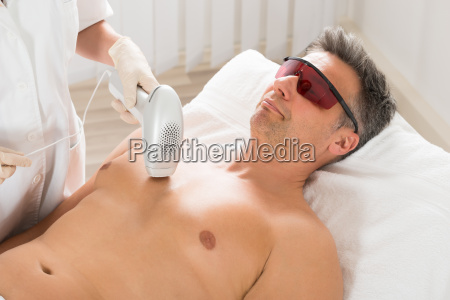 beautician giving laser epilation treatment to