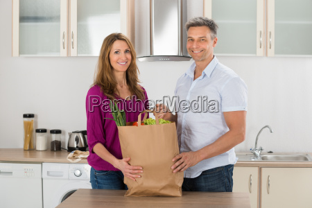 happy couple holding grocery bag