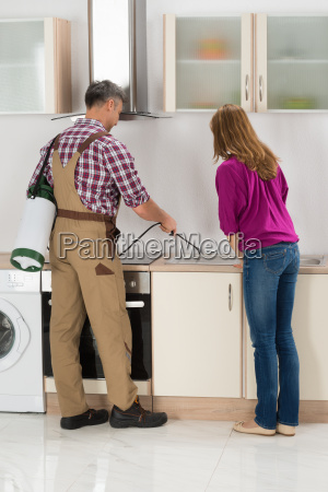 worker spraying insecticide in kitchen