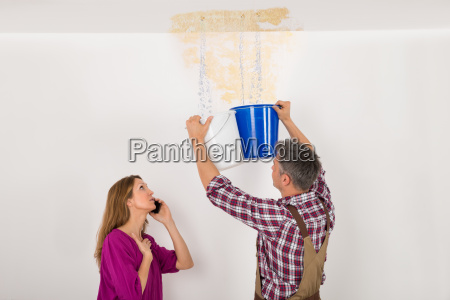 worker collecting water in bucket from