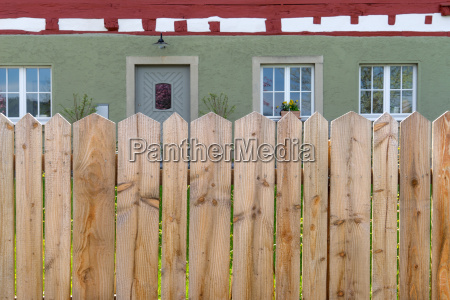 wooden fence with house behind it