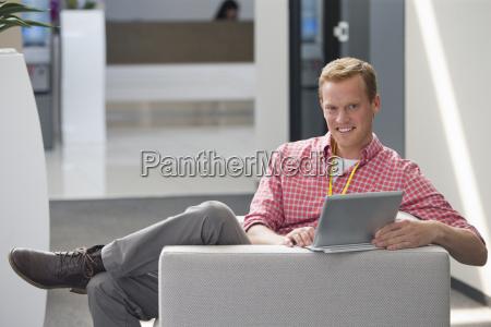 man sitting on sofa working on