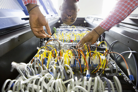 technician checking wiring of server in