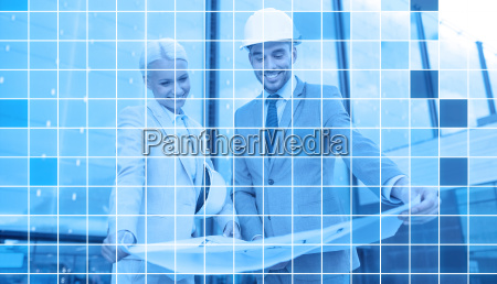 smiling business people in helmets with