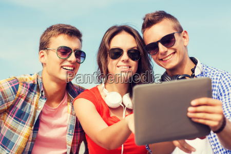 group of smiling friends with tablet