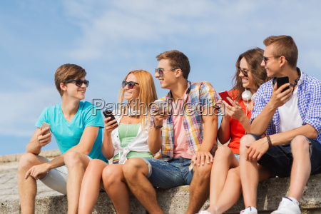 group of smiling friends with smartphones
