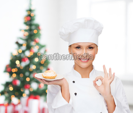 smiling female chef with cupcake on