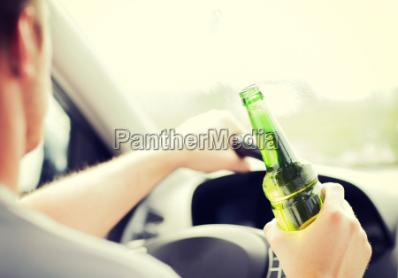 man drinking alcohol while driving the