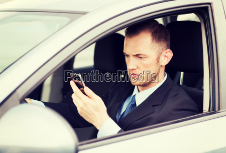 man using phone while driving the