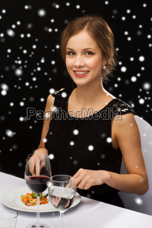 smiling woman with tablet pc eating
