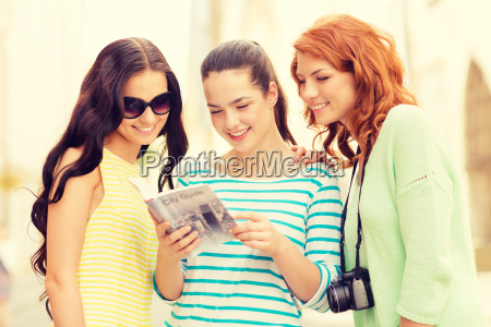 smiling teenage girls with city guide