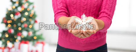 close up of woman holding snowflake