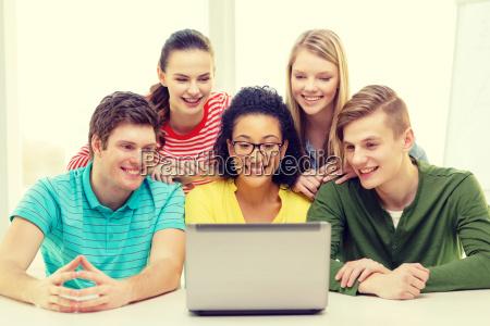 smiling students looking at laptop at