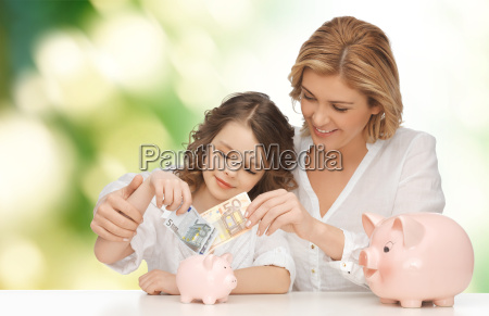 mother and daughter putting money to