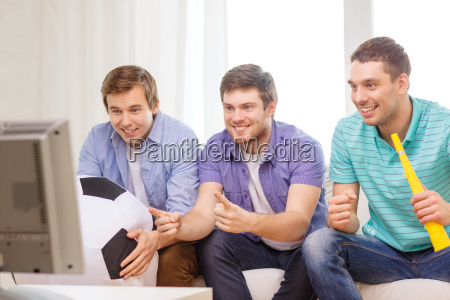 happy male friends with football and