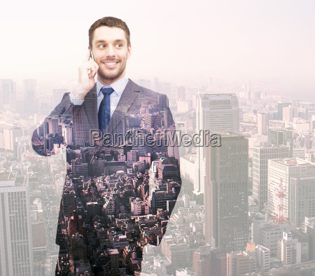 smiling young businessman over city background