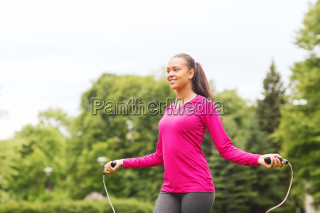 smiling woman exercising with jump rope