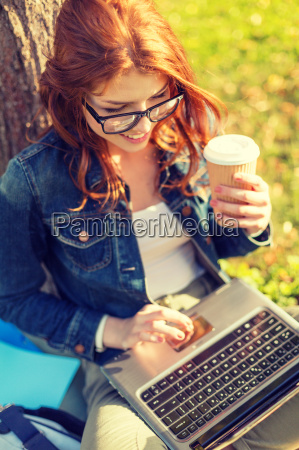teenager in eyeglasses with laptop and