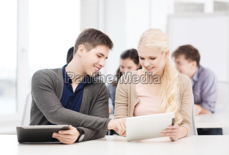 students looking at tablet pc in