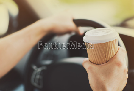 man drinking coffee while driving the