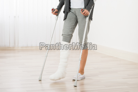woman using crutches while walking