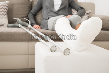 woman with plastered leg sitting on