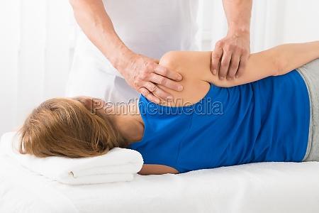 masseur doing arm massage in spa