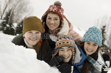 winter snow four children grouped laughing