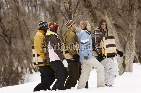 five young people carrying a wooden