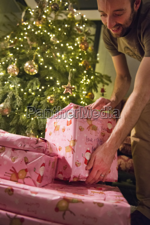 a man stacking wrapped presents under