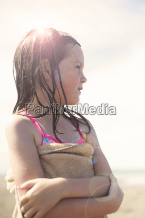 girl wrapped in towel after swimming