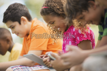a row of children sitting outdoors