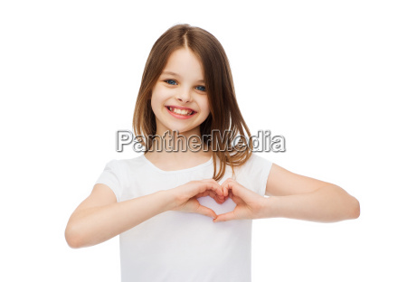 smiling little girl showing heart with
