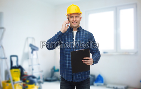 smiling builder in helmet calling on