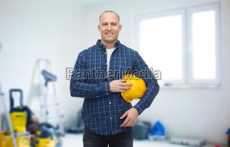 smiling man holding helmet over room