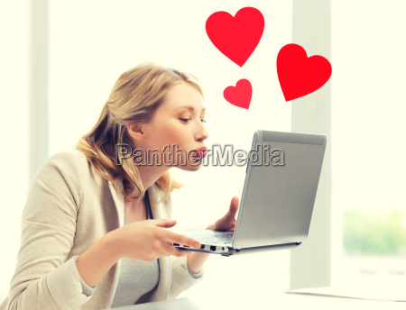 woman sending kisses with laptop computer