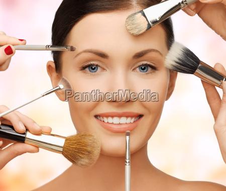 happy woman applying professional make up