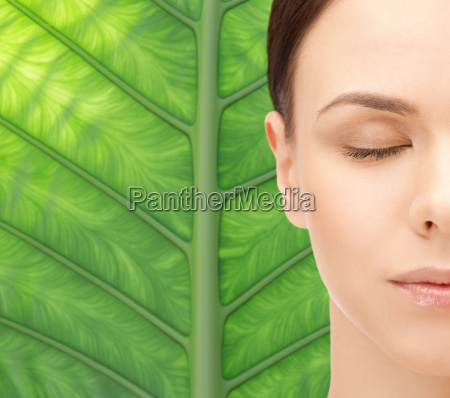 young woman face over green leaf