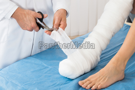 doctor bandaging leg of patient