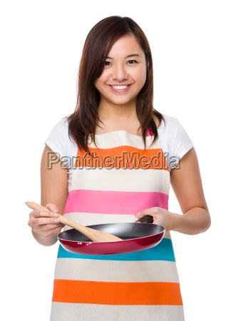 young housewife cooking with frying pan