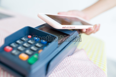 woman paying with nfc technology on
